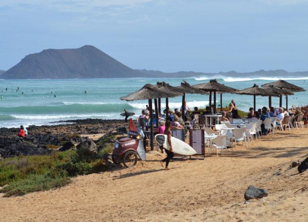 Sonnenschirme am Strand mit Surfern