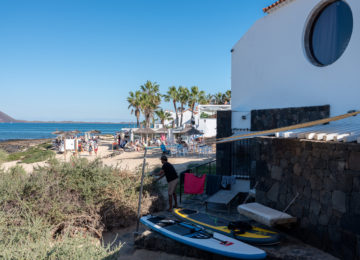 Exterior view of surf camp with surfboards