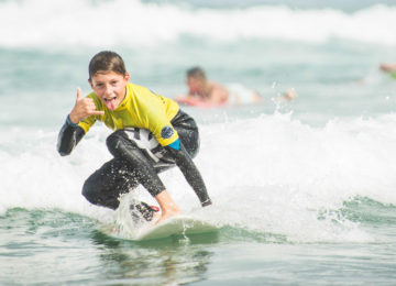 Surfer makes the Shaka greeting while surfing