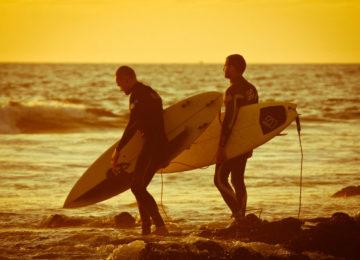 Zwei Surfer laufen über die Steine am Strand