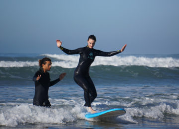 The surf coach helps the surf student to the first success