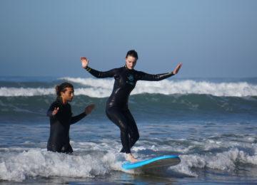 Der Surfcoach hilft der Surfschülerin zum ersten Erfolg