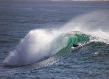 A surfer paddles into the wave