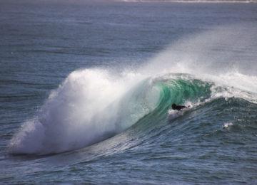 Ein Surfer paddelt in die Welle rein