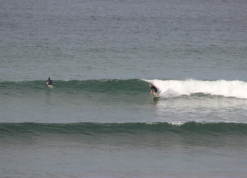 A surfer rides a right wave