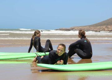Zwei sitzende Surferinnen und ein Sonnenschein die in die Kamera lächelt