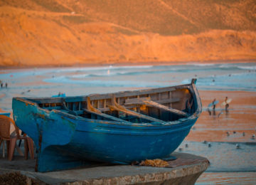 An old fishing boat lies in front of the surf bay