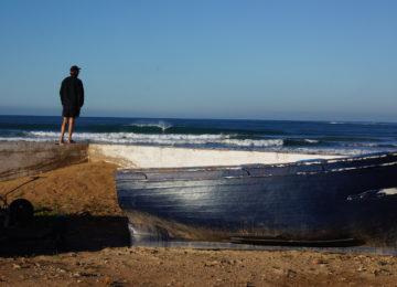 Ein Herr schaut sich die Wellen am Strand an