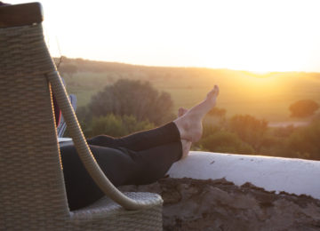 A person sits in a chair and enjoys the sunset