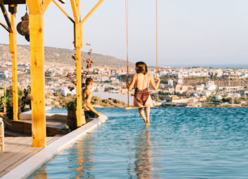 A woman on the swing above the swimming pool