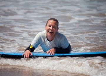 Lachende Surferin auf dem Brett
