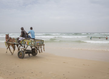 Carriage on the beach and surfers in the water