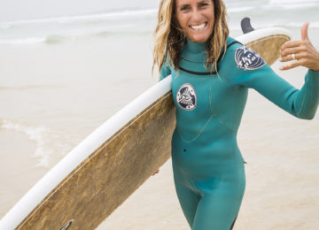 Cheerful surf trainer waves to the camera with Shaka sign