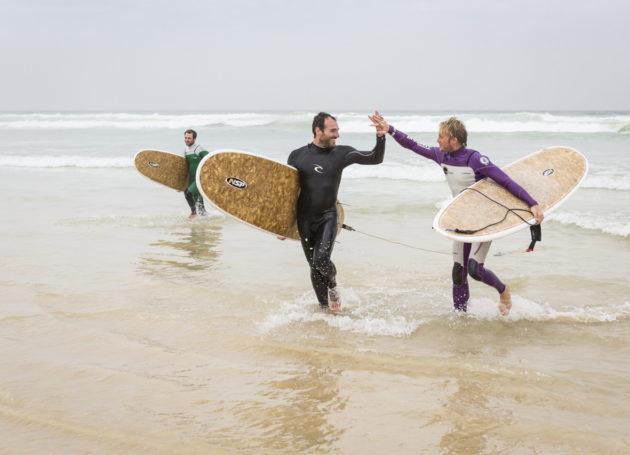 Fröhliche Surfanfänger klatschen in die Hände