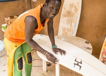 Einheimischer Surfer repariert Surfbrett