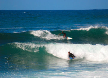 Surfers and bodyboarders ride the waves