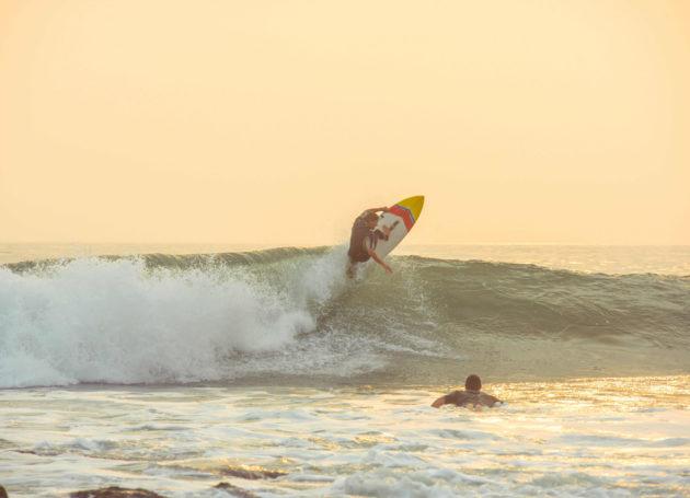 Surfer mit Manöver in der Welle
