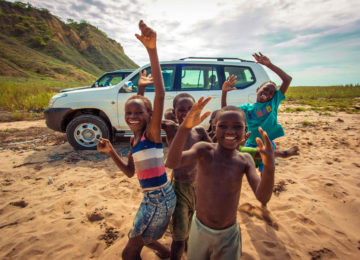 Indigenous children from Angola wave in camera