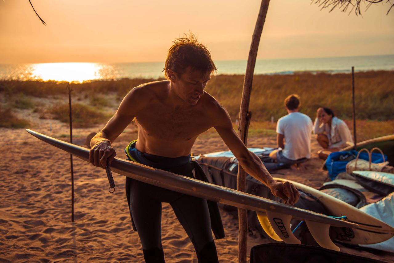 Surfer waxes his surfboard