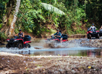 A group rides quads through a creek