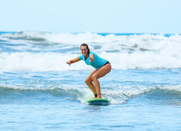 A beginner stands on the surfboard