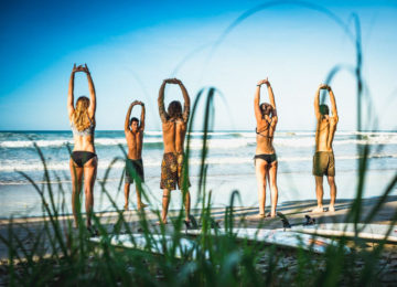 A group does exercises on the beach before surfing