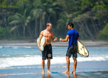 Two surfers salute on the beach
