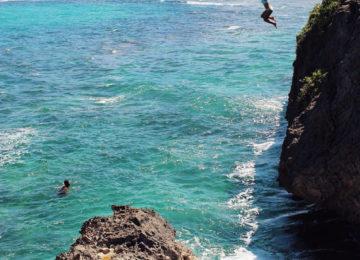 Gast spring von Klippe ins Meer