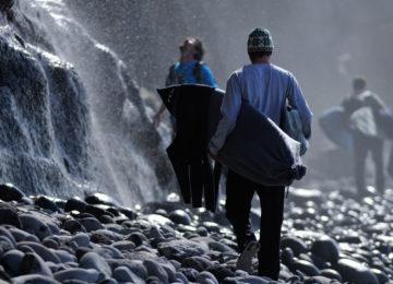 Surfer laufen über Steine an einem Wasserfall vorbei