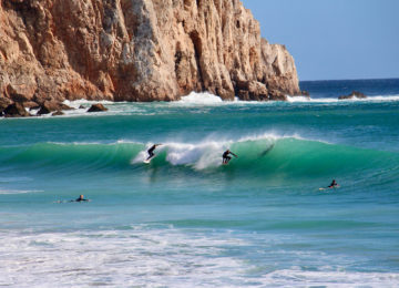 Surfers surfing wave in the Algarve