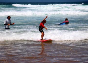 Child surfs foam wave