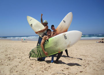 Dodo and surfer with surfboard on the beach