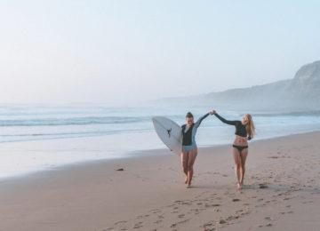 Zwei gehende Frauen halten sich am Strand die Hände