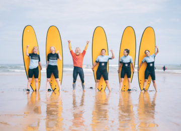 Surf students in front of the surfboard