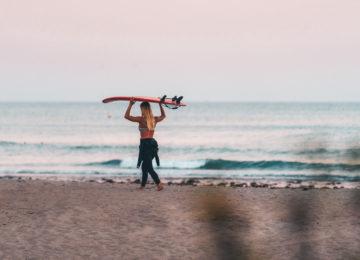 Surferin am Strand mit Board auf Kopf