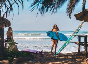 Surferin mit Board am Spot