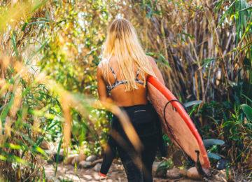 Surferin auf dem Weg zum Surfspot