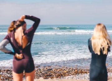 Gäste blicken am Strand auf die Welle