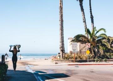 Surferin läuft mit Surfboard an den Strand