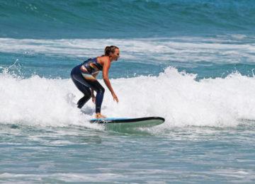 Surfer surfs wave in surf course