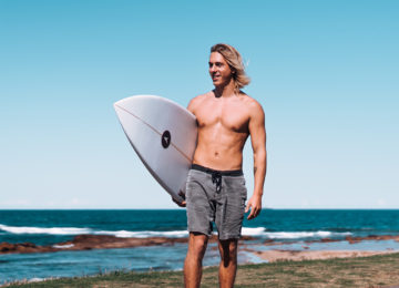 Surfer rides on the skateboard to the surf spot