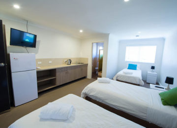 Multi-bed room with kitchenette and TV