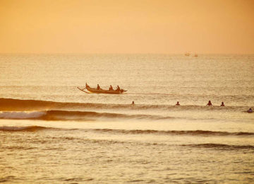 Sunset lineup with surfer and local fishing boat