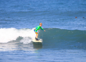 Child surfs green wave in Bali