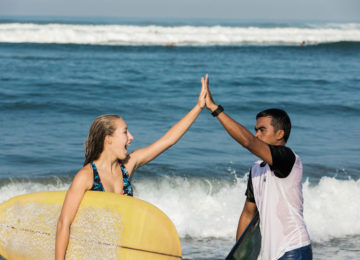 Happy surfer with surf coach