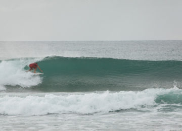 Surfers in barrels in the Moluccas