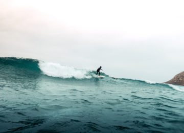 A surfer rides down the wave