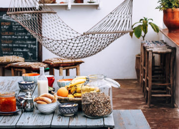 A laid table for breakfast and a hammock in the background