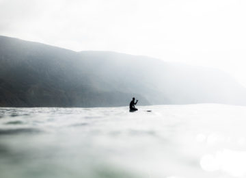 Surfer sits in the water on the board and waves in camera