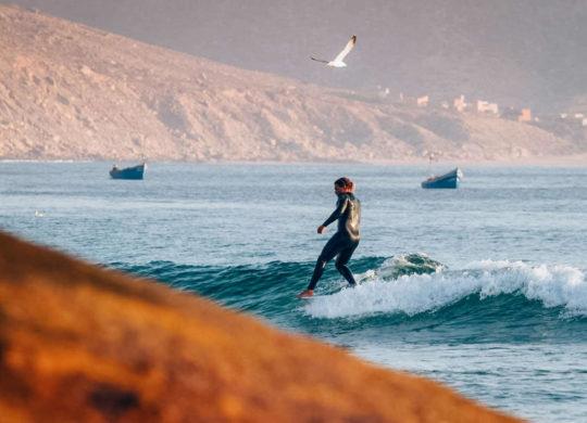 Surferin von Nah mit Hang Five Trick auf Surfbrett
